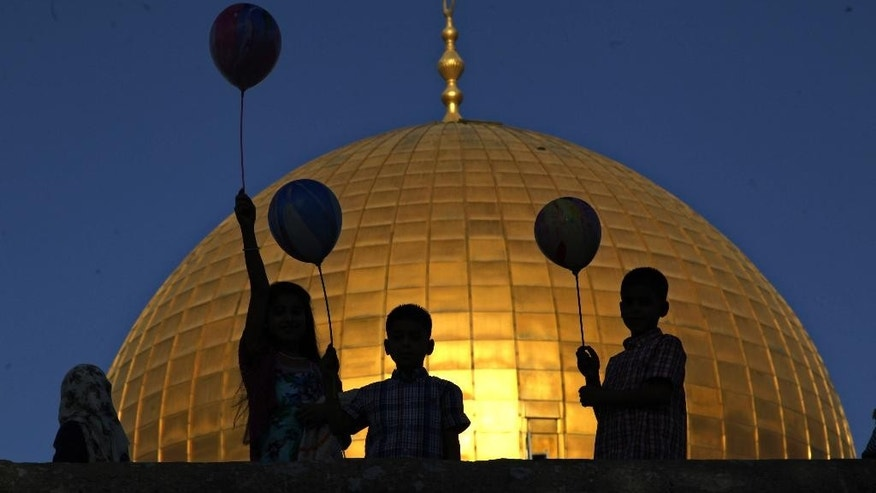 Palestinian children hold balloons during the Muslim holiday of Eid al-Adha, near the Dome of the Rock Mosque in the Al Aqsa Mosque compound in Jerusalem's old city, Thursday, Sept. 24, 2015. Muslims will slaughter cattle and goats later, with the beef and meat distributed to the needy in the holiday which honors the prophet Abraham for preparing to sacrifice his son on the order of God, who was testing his faith. (AP Photo/Mahmoud Illean)