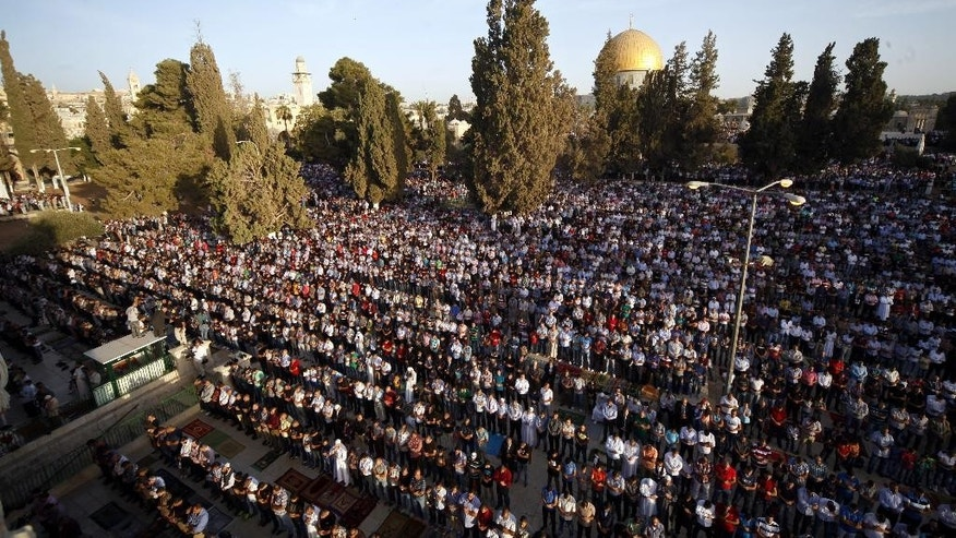 Palestinian pray during the Muslim holiday of Eid al-Adha, near the Dome of the Rock Mosque in the Al Aqsa Mosque compound in Jerusalem's old city, Thursday, Sept. 24, 2015. Muslims will slaughter cattle and goats later, with the beef and meat distributed to the needy in the holiday which honors the prophet Abraham for preparing to sacrifice his son on the order of God, who was testing his faith. (AP Photo/Mahmoud Illean)