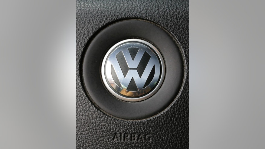 The VW logo sits on the steering wheel of a Volkswagen Passat in Nauen, Germany, Thursday, Sept. 24, 2015. The software at the center of Volkswagen's emissions scandal in the U.S. was built into the automaker's cars in Europe as well, though it isn't yet clear if it helped cheat tests as it did in the U.S., Germany said Thursday. A day after longtime CEO Martin Winterkorn stepped down, a member of Volkswagen's supervisory board said that he expects further resignations at the automaker in the wake of the scandal. (AP Photo/Ferdinand Ostrop)
