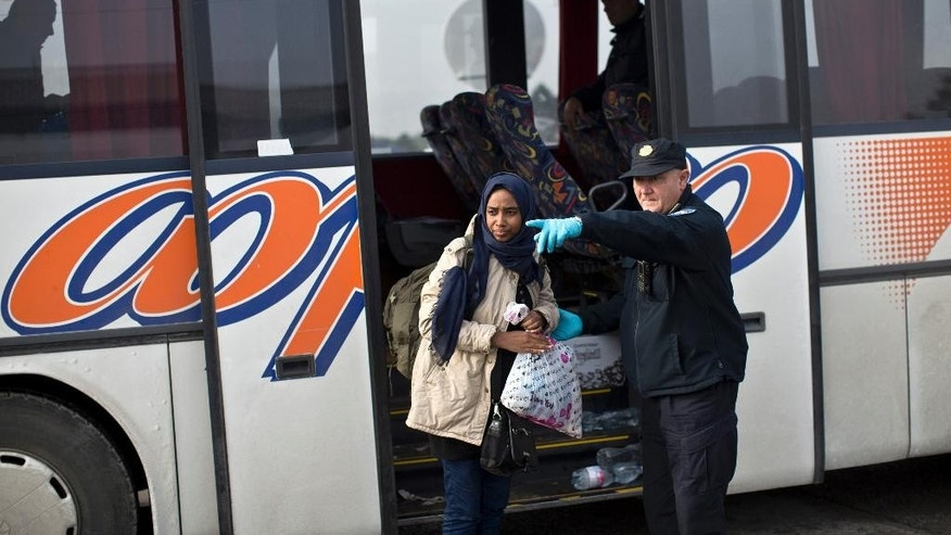 A Croatian police officer shows the way to a woman as she exits a bus in front of a registration center for migrants and refugees in Opatovac, Croatia, Thursday, Sept. 24, 2015. Serbia has banned imports of Croatian goods and Croatia has retaliated by barring vehicles with Serbian license plates from entering the country as relations between the two Balkan neighbors deteriorated over the influx of migrants over their border. (AP Photo/Marko Drobnjakovic)