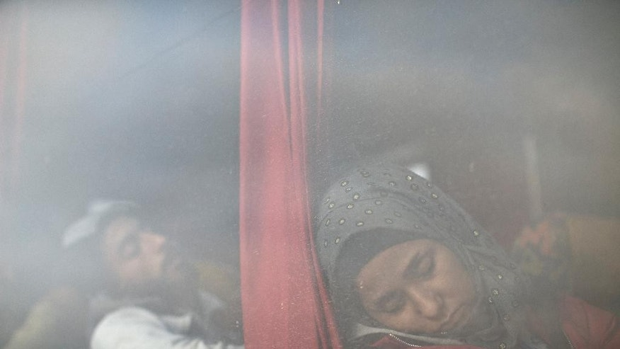 Migrants sleep inside a bus as they wait to be admitted into a registration center for migrants and refugees in Opatovac, Croatia, Thursday, Sept. 24, 2015. Serbia has banned imports of Croatian goods and Croatia has retaliated by barring vehicles with Serbian license plates from entering the country as relations between the two Balkan neighbors deteriorated over the influx of migrants over their border. (AP Photo/Marko Drobnjakovic)