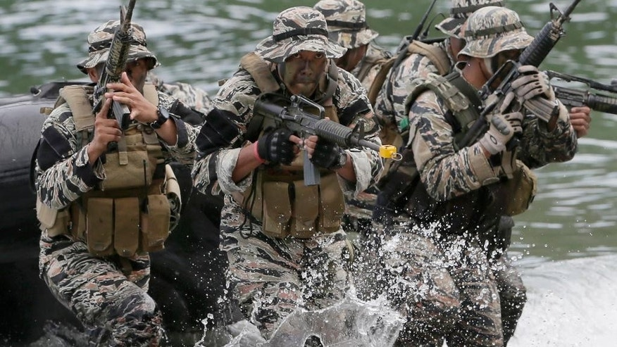 "Philippine Marines from the Naval Special Operations Group (NAVSOG) storm the beach to simulate an ""extraction"" of a kidnapped victim as they kick off a five-day amphibious military exercise at the Philippine Marines training center in Ternate, Cavite province, about 50 miles (80kms) south of Manila, Philippines Thursday, Sept. 24, 2015. The naval exercise dubbed PAGSISIKAP 2015 is aimed at enhancing capability of their fleet and forces as well as to strengthen interoperability of the Marines. (AP Photo/Bullit Marquez)"