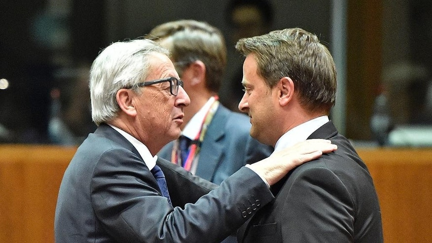 European Commission President Jean-Claude Juncker, left, embraces Luxembourg's Prime Minister Xavier Bettel during an emergency EU heads of state summit on the migrant crisis at the EU Commission headquarters in Brussels on Wednesday, Sept. 23, 2015.  (AP Photo/Martin Meissner)