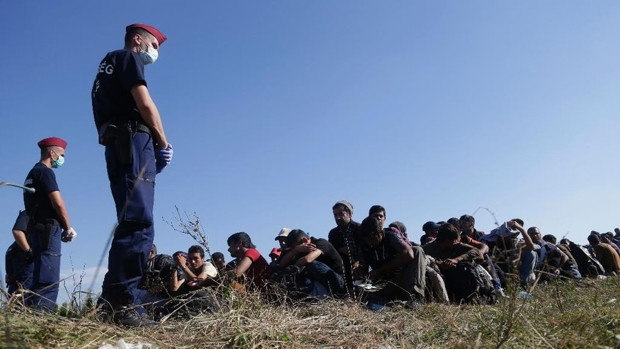 A group of migrants sits and waits to be escorted to a train after crossing a border from Croatia near the village of Zakany, Hungary, Wednesday, Sept. 23, 2015. Deeply divided European Union leaders have been called to an emergency summit to seek long-term responses to the continent's ballooning crisis of refugees and migrants, a historic challenge EU President Donald Tusk said the bloc has failed dismally to meet. (AP Photo/Petr David Josek)