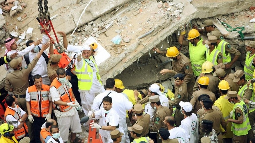 FILE - In this Jan. 5, 2006 file photo, rescuers attend to the scene of a building collapse in Mecca, Saudi Arabia. The day before the hajj began, an eight-story building being used as a hostel near the Grand Mosque in Mecca collapsed, killing at least 73 people and injuring 62. (AP Photo, File)
