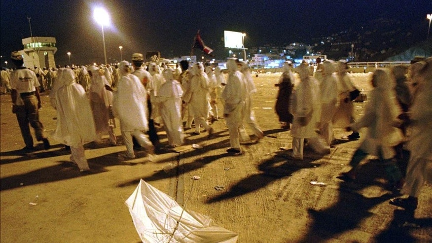 "FILE - In this April 9, 1998 file photo, pilgrims walk past a broken umbrella left on the ground at the site of a stampede that left more than 150 people dead at Mina, Saudi Arabia. The stampede broke out as Muslims rushed to perform a religious duty known as ""stoning the devil"", where supplicants hurl stones at pillars symbolizing the temptations of Satan. (AP Photo/Kamran Jebreili, File)"