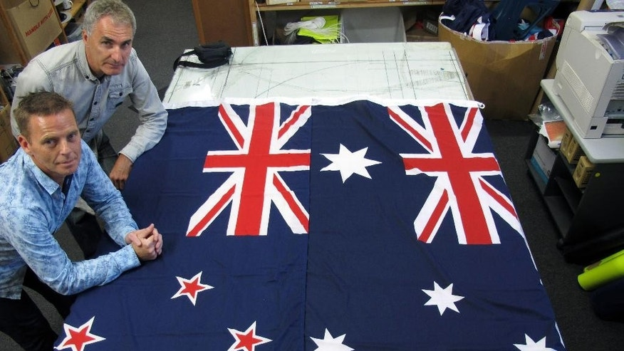 "In this March 3, 2014, file photo, Victor Gizzi, left, and David Moginie, managers at flag manufacturer Flagmakers, pose next to flags of New Zealand, left, and Australia, in their factory near Wellington, New Zealand. New Zealanders now have a fifth option to choose from when deciding whether to change their flag after a popular campaign for a geometric design called ""Red Peak"" prompted lawmakers to change the rules to add it to the original four finalists.The flag that wins in November will be pitted head-to-head against the current flag in a second nationwide vote next March. (AP Photo/Nick Perry, File)"