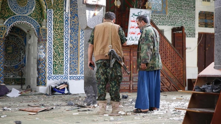 Shiite fighters, known as Houthis inspect the inside of the al-Balili mosque after two suicide bombings at the mosque during Eid al-Adha prayers in Sanaa, Yemen, Thursday, Sept. 24, 2015. (AP Photo/Hani Mohammed)