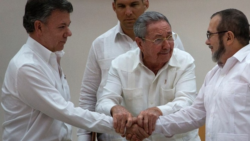 Cuba's President Raul Castro, center, encourages Colombian President Juan Manuel Santos, left, and Commander the Revolutionary Armed Forces of Colombia or FARC, Timoleon Jimenez to shake hands, in Havana, Cuba, Wednesday, Sept. 23, 2015. In a joint statement, Santos and the FARC said they have overcome the last significant obstacle to a peace deal by settling on a formula to compensate victims and punish belligerents for human rights abuses. (AP Photo/Desmond Boylan)