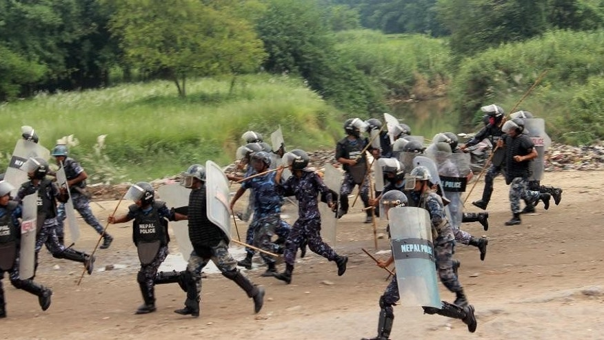 Nepalese policemen run for cover as they are chased by protestors belonging to ethnic and religious groups dissatisfied with Nepal's new constitution adopted on Sunday, in Birgunj, a town bordering India in Nepal, Thursday, Sept. 24, 2015. Nepal's top political parties on Thursday reached out to protesters angry about the country's new constitution, after violence in the region bordering India halted more than 1,000 oil tankers and trucks with essential supplies from entering Nepal. (AP Photo/ Jiyalal Sah)