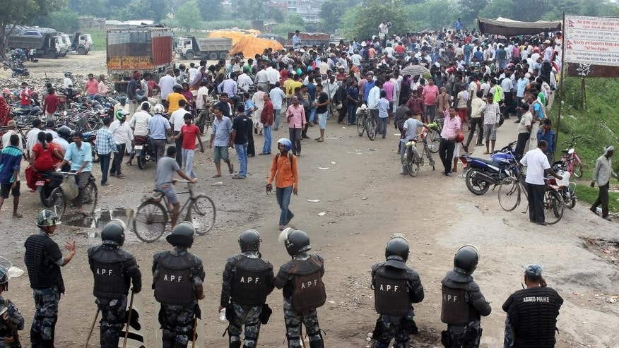 Nepalese policemen face protestors belonging to ethnic and religious groups dissatisfied with Nepal's new constitution adopted on Sunday, in Birgunj, a town bordering India in Nepal, Thursday, Sept. 24, 2015. Nepal's top political parties on Thursday reached out to protesters angry about the country's new constitution, after violence in the region bordering India halted more than 1,000 oil tankers and trucks with essential supplies from entering Nepal. (AP Photo/ Jiyalal Sah)