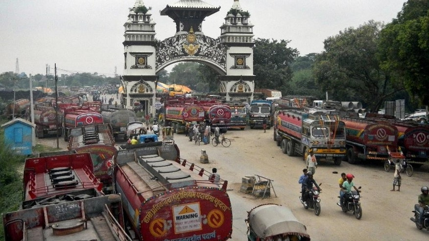 Nepalese oil tankers and commercial trucks stand stranded near a gate that marks the Nepalese border with India, in Birgunj, Nepal, Thursday, Sept. 24, 2015. Nepal's top political parties on Thursday reached out to protesters angry about the country's new constitution, after violence in the region bordering India halted more than 1,000 oil tankers and trucks with essential supplies from entering Nepal. The disruption of traffic has raised fear of shortages in the Himalayan nation. (AP Photo/Ram Sarraf)