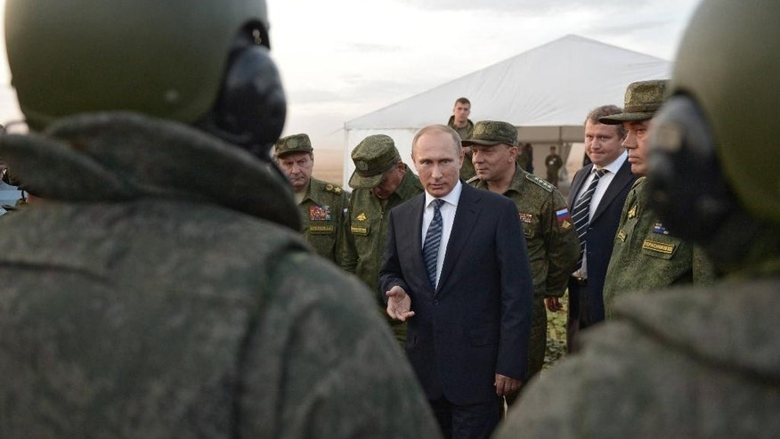 FILE -  In this Saturday, Sept. 19, 2015 file pool photo, Russian President Vladimir Putin, center, meets with officers after military exercises at Donguz range in Orenburg region, Russia. With dozens of Russian combat jets and helicopter gunships lined up at an air base in Syria, Russian President Vladimir Putin is ready for a big-time show at the United Nations General Assembly. Observers expect the Russian leader to call for stronger U.N.-sanctioned global action against the Islamic State group and possibly announce some military moves in his speech on Monday, Sept. 28, 2015. (Alexei Nikolsky/RIA-Novosti, Kremlin Pool Photo via AP, file)