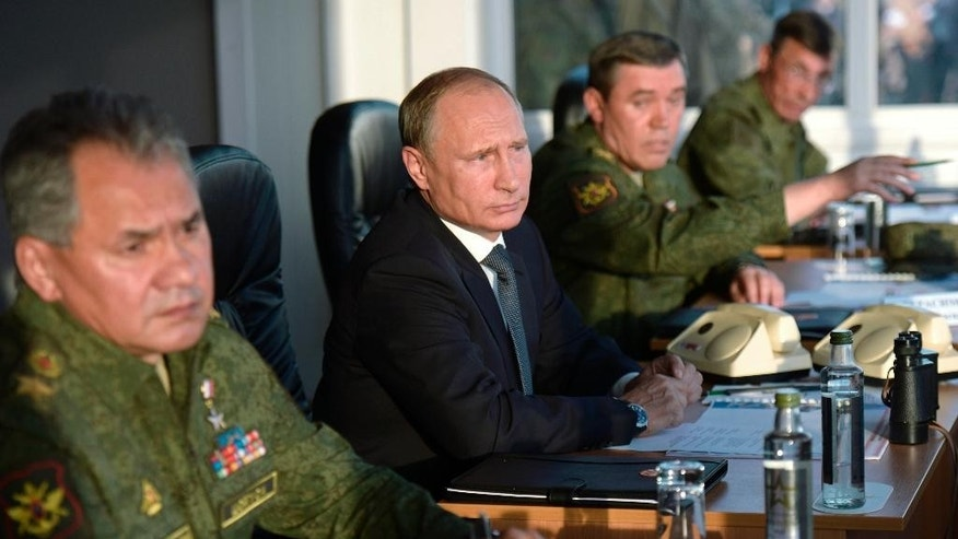FILE - In this Saturday, Sept. 19, 2015 file pool photo, Russian President Vladimir Putin, second left, flanked by Defense Minister Sergei Shoigu, left, and Chief of the General Staff of the Russian Armed Forces Valery Gerasimov, watches military exercises at Donguz range in Orenburg region, Russia. With dozens of Russian combat jets and helicopter gunships lined up at an air base in Syria, Russian President Vladimir Putin is ready for a big-time show at the United Nations General Assembly. Observers expect the Russian leader to call for stronger U.N.-sanctioned global action against the Islamic State group and possibly announce some military moves in his speech on Monday, Sept. 28, 2015. (Alexei Nikolsky/RIA-Novosti, Kremlin Pool Photo via AP, file)