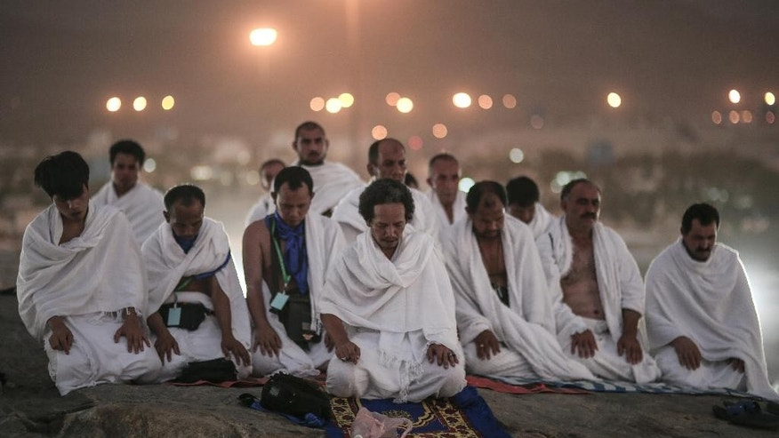 Muslim pilgrims pray on a rocky hill called the Mountain of Mercy, on the Plain of Arafat, near the holy city of Mecca, Saudi Arabia, Tuesday, Sept. 22, 2015. Mount Arafat, marked by a white pillar, is where Islam's Prophet Muhammad is believed to have delivered his last sermon to tens of thousands of followers some 1,400 years ago, calling on Muslims to unite. (AP Photo/Mosa'ab Elshamy)