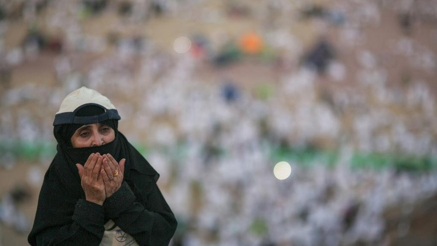 A Muslim pilgrim prays on a rocky hill called the Mountain of Mercy, on the Plain of Arafat, near the holy city of Mecca, Saudi Arabia, Wednesday, Sept. 23, 2015 during the hajj pilgrimage. Mount Arafat, marked by a white pillar, is where Islam's Prophet Muhammad is believed to have delivered his last sermon to tens of thousands of followers some 1,400 years ago, calling on Muslims to unite. (AP Photo/Mosa'ab Elshamy)
