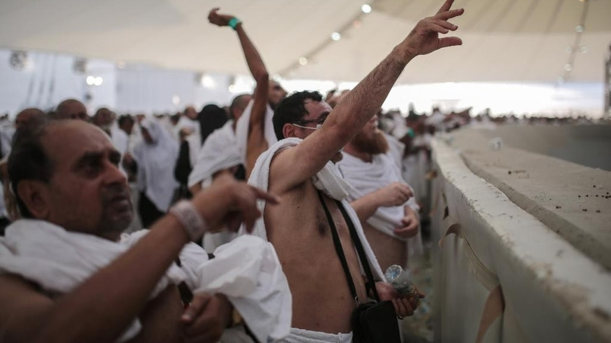 "Muslim pilgrims cast stones at a pillar symbolizing the stoning of Satan, in a ritual called ""Jamarat,"" the last rite of the annual hajj, on the first day of Eid al-Adha, in Mina near the holy city of Mecca, Saudi Arabia, Thursday, Sept. 24, 2015. Saudi Arabia's civil defense directorate says at least 150 people have been killed in a stampede at the annual hajj pilgrimage. (AP Photo/Mosa'ab Elshamy)"
