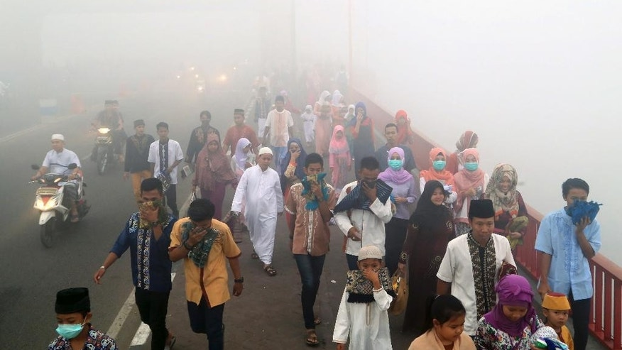 Muslims cover their mouths and noses from the haze from wildfires as they walk to attend a morning prayer marking the Eid al-Adha in Palembang, South Sumatra, Indonesia, Thursday, Sept. 24, 2015. Slash-and-burn practices destroy huge areas of Indonesian forest every summer during the dry season, creating haze that blankets parts of the archipelago and neighboring Malaysia and Singapore. (AP Photo)