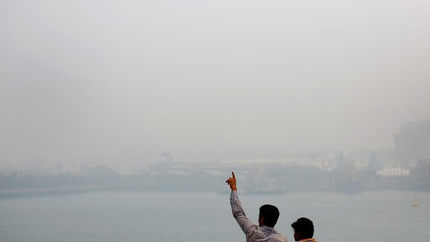 Two men look across the sea towards Singapore's popular tourist destination, Sentosa, which is hardly visible due to the haze, Thursday, Sept. 24, 2015, in Singapore. Slash-and-burn practices destroy huge areas of Indonesian forest every summer during the dry season, creating haze that angers surrounding countries. The fires are set to clear land for farming, corporate development or oil palm plantations. (AP Photo/Wong Maye-E)