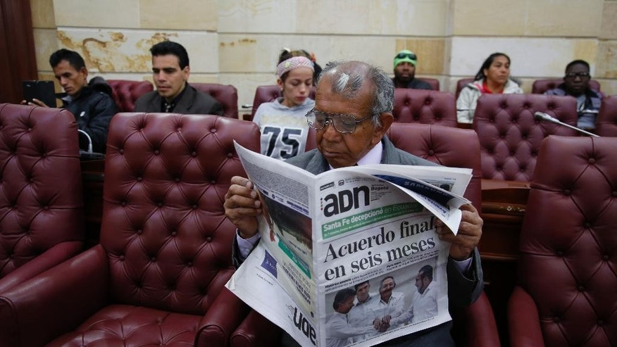 "Pedro Osuna Ramirez, 67, who says that he and his family were pushed from their land in central Colombia by rebels of the Revolutionary Armed Forces of Colombia, FARC, reads a newspaper during a hearing with victims of the guerrilla group inside Congress in Bogota, Colombia, Thursday, Sept. 24, 2015. Colombia's President Juan Manuel Santos and leaders of the FARC met in Havana on Wednesday, and vowed to end Latin America's longest-running armed conflict in the coming months. The newspaper's headline reads in Spanish ""Final agreement in six months."" (AP Photo/Fernando Vergara)"