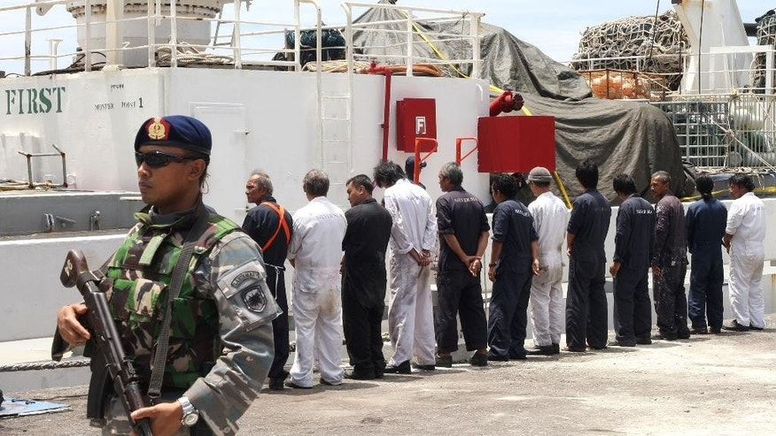CORRECTS THE NUMBER OF THAIS ARRESTED TO ONE (THE SHIP'S CAPTAIN), INSTEAD OF THREE - Navy personnel stand guard as the crew of Silver Sea 2, a Thai-owned cargo ship which was seized by Indonesian authorities last August, are lined up during a media conference at the port of Sabang, Aceh province, Indonesia, Friday, Sept. 25, 2015. The Thai captain of the ship has been arrested in Indonesia following allegations of illegal fishing, an official said Friday. It is the latest development linked to an Associated Press investigation that uncovered a slave island earlier this year. (AP Photo/Heri Juanda)