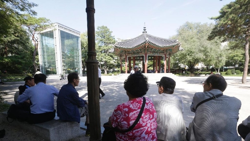 In this Sept. 15, 2015 photo, elderly people sit in the shade at Tapgol park in Seoul, South Korea. The park, mostly a place for relaxation for elderly residents in Seoul, had also been a site where elderly prostitutes solicit customers for sex in nearby motels. After widespread police crackdown this spring, many elderly prostitutes have disappeared in Seoul but some still operate near a plaza in front of the Piccadilly theater, which is about 10 minutes' walk from Tapgol Park.(AP Photo/Ahn Young-joon)