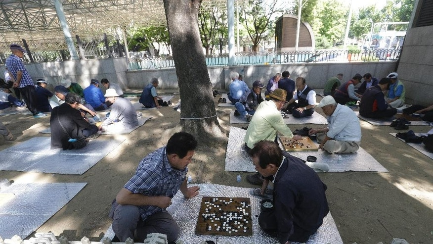 "In this Sept. 15, 2015 photo, elderly people play Go or ""baduk,"" a traditional board game, at Jongmyo park in Seoul, South Korea. The park had been the main hotspot for elderly prostitutes, dubbed ""Bacchus ladies"" after the popular energy drink that they have traditionally sold. After widespread police crackdowns this spring that resulted in 33 arrests, elderly prostitutes at Jongmyo park have disappeared. But some still troll for men near the Piccadilly theater, which is close to Jongmyo park.(AP Photo/Ahn Young-joon)"