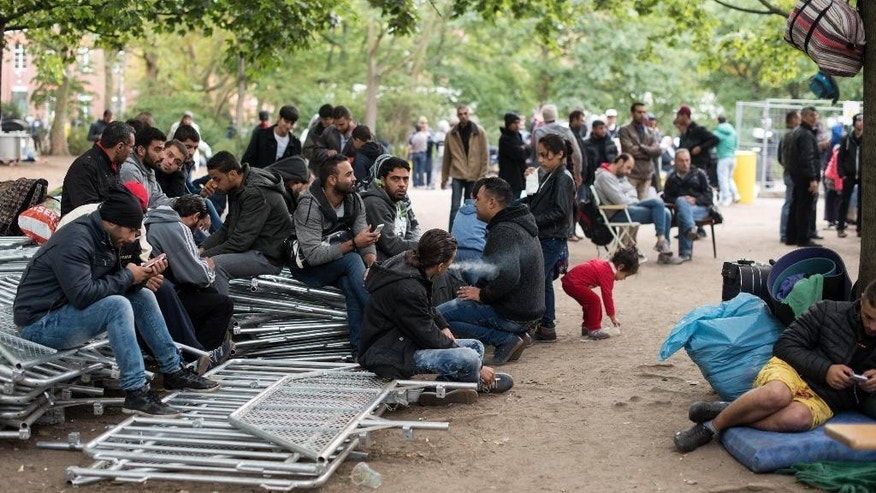 Refugees wait for registration outside the state office for health and social issues in Berlin, Germany, Friday, Sept. 25 2015. Every day hundreds of refugees have to wait here to be registered. (Bernd von Jutrczenka/dpa via AP)