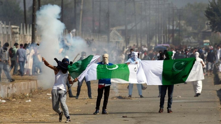 Masked Kashmiris hold the national flag of Pakistan during a protest outside Eidgha, a prayer ground, in Srinagar, Indian controlled Kashmir, Friday, Sept. 25, 2015. Police fired teargas and rubber bullets to disperse hundreds of Kashmiris who gathered after special Eid prayers to protest a court ruling upholding a colonial-era law banning cow slaughter and the sale of beef in the Indian-controlled portion of Kashmir. (AP Photo/Dar Yasin)