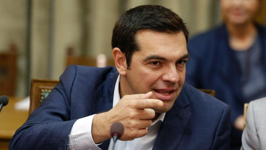 Greece's Prime Minister Alexis Tsipras gestures as he leads the first cabinet meeting of his new government in Athens, Friday, Sept. 25, 2015. Tsipras, at 41 Greece's youngest prime minister in about 150 years, won re-election in the early election despite a rebellion in his party after his remarkable policy U-turn in the summer, when he broke key promises to fight bailout-linked austerity and instead signed a new bailout with even more tax hikes and income cuts. (AP Photo/Thanassis Stavrakis)