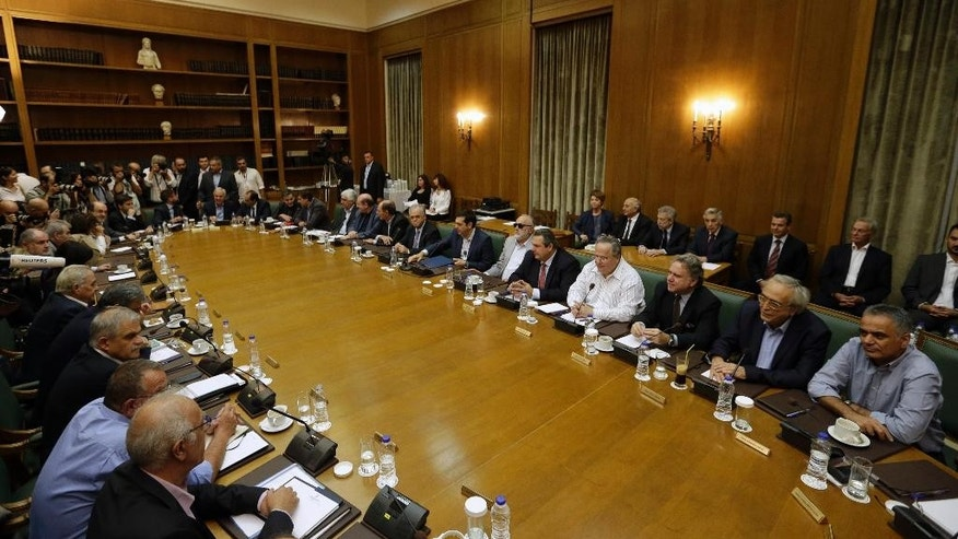 Members of the new government attend the first cabinet meeting in Athens, Friday, Sept. 25, 2015. Greece's Prime Minister Alexis Tsipras, at 41 Greece's youngest prime minister in about 150 years, won re-election in the early election despite a rebellion in his party after his remarkable policy U-turn in the summer, when he broke key promises to fight bailout-linked austerity and instead signed a new bailout with even more tax hikes and income cuts. (AP Photo/Thanassis Stavrakis)