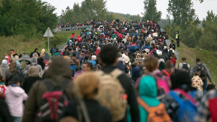 Migrants walk across a bridge in Botovo,  Croatia near thr  Hungarian border,   Thursday, Sept. 24, 2015. Croatia says it's so overwhelmed that authorities have been shipping the migrants toward Hungary or Slovenia. Most want to travel on to wealthier nations in Western Europe such as Germany or Sweden. (AP Photo/Darko Bandic)
