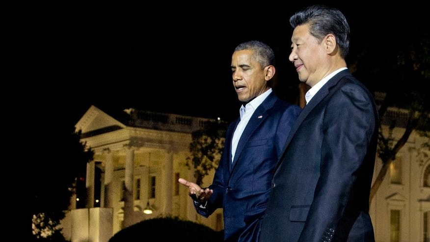 In this Thursday, Sept. 24, 2015, file photo, U.S. President Barack Obama and Chinese President Xi Jinping, right, walk on the North Lawn of the White House in Washington, as they head for a private dinner at the Blair House, across the street from the White House. U.S.-China relations have never been rosier -- that is how Chinese state media is presenting Xi's U.S. trip, which is being followed with great interest from his visits to Boeing and tech giants to going on an evening stroll with Obama on the White House grounds without their ties. (AP Photo/Manuel Balce Ceneta, File)