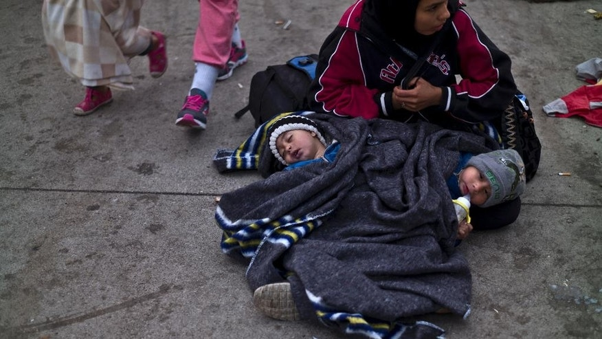 An Afghan refugee woman sits on the ground with her twin sons, Othman Abdulghafar, 2, right, and Irafan, sleeping by wrapped with a blanket to shelter from the morning cold after spending the night at a collection point in the truck parking lot of the former border station on the Austrian side of the Hungarian-Austrian border near Nickelsdorf, Austria, Friday, Sept. 25, 2015. Deeply divided European Union leaders held an emergency summit to seek long-term responses to the continent's ballooning crisis of refugees and migrants, a historic challenge EU President Donald Tusk said the bloc has failed dismally to meet. (AP Photo/Muhammed Muheisen)