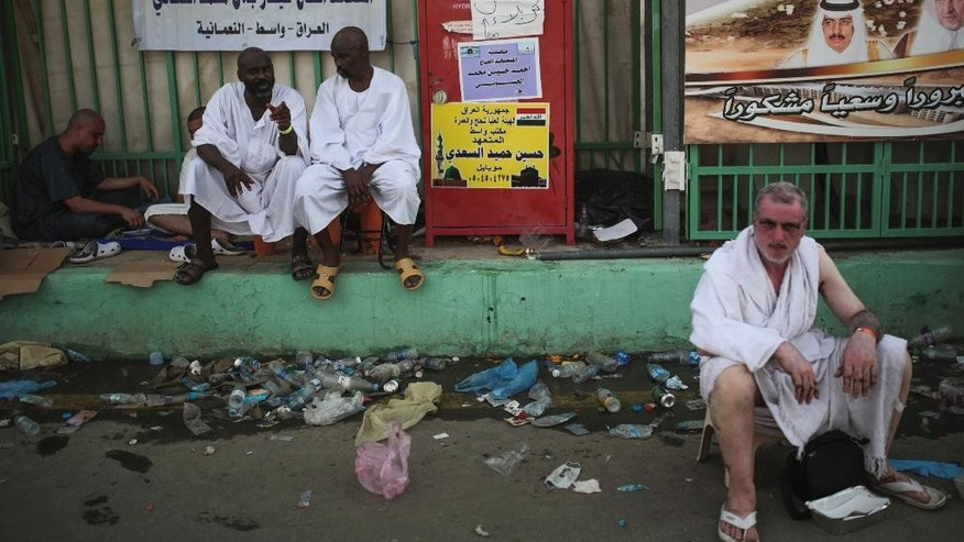 Muslim pilgrims sit by the site where pilgrims were crushed and trampled to death during the annual hajj pilgrimage in Mina, Saudi Arabia, Thursday, Sept. 24, 2015. The crush killed hundreds of pilgrims and injured hundreds more in Mina, a large valley on the outskirts of the holy city of Mecca, the deadliest tragedy to strike the pilgrimage in more than two decades. (AP Photo/Mosa'ab Elshamy)