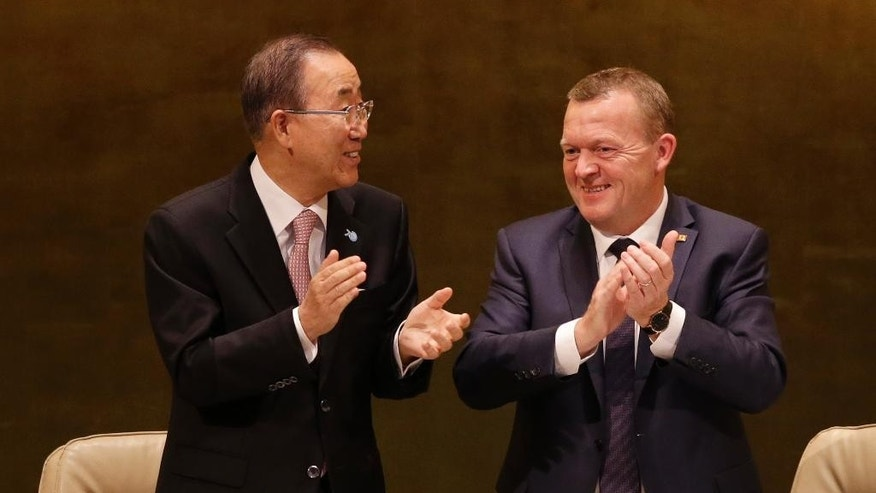 Danish Prime Minister Lars Lokke Rasmussen, right, and United Nations Secretary-General Ban Ki-moon celebrate after the passing of a draft resolution during the 2015 Sustainable Development Summit, Friday, Sept. 25, 2015 at United Nations headquarters. (AP Photo/Seth Wenig)