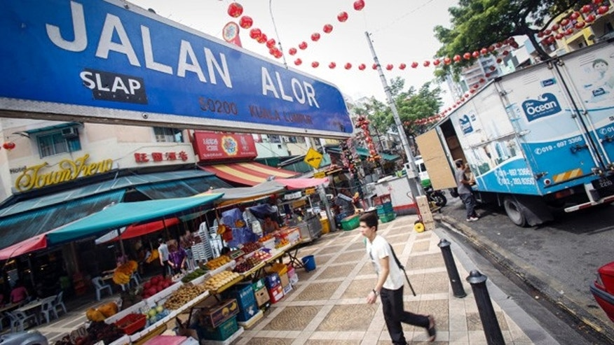 Sept. 25, 2015: A tourist walks past Malaysia's famous eatery street, Jalan Alor, a popular tourist spot in Kuala Lumpur. The U.S. Embassy issued an advisory Thursday saying it has credible threat information and urged its citizens to avoid Alor Street, located in a shopping belt in the city center, and its immediate surrounding areas. (AP Photo/Joshua Paul)