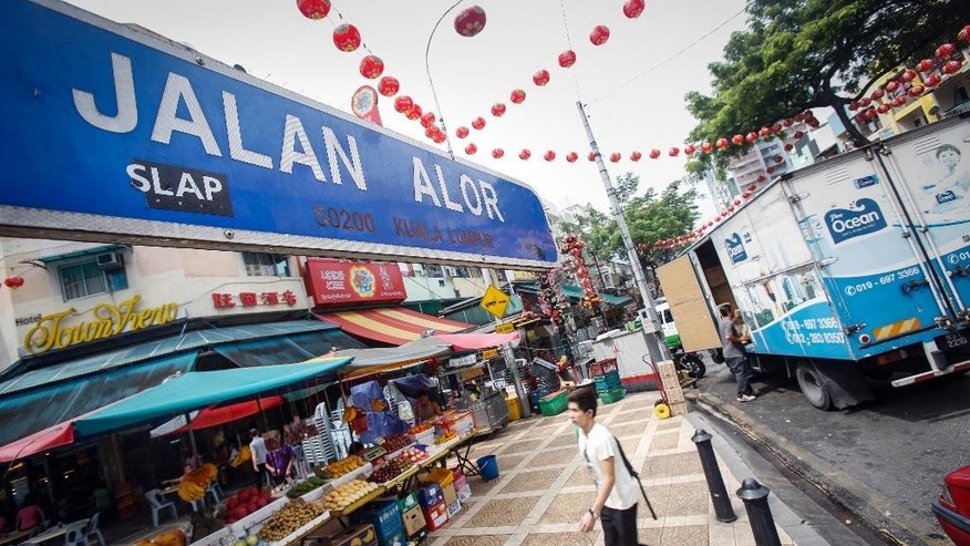A tourist walks past Malaysia's famous eatery street, Jalan Alor, a popular tourist spot in Kuala Lumpur, Malaysia on Friday, Sept. 25, 2015. The U.S. Embassy issued an advisory Thursday saying it has credible threat information and urged its citizens to avoid Alor Street, located in a shopping belt in the city center, and its immediate surrounding areas. (AP Photo/Joshua Paul)