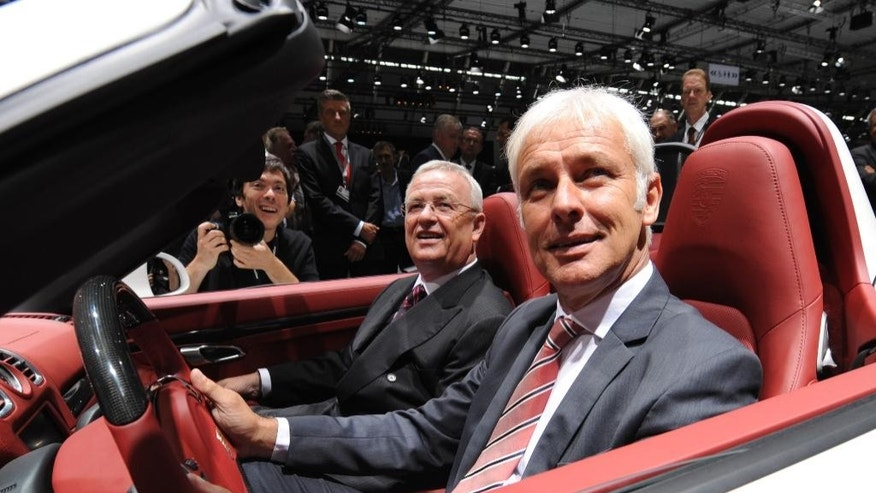 FILE - In this June 25, 2012 file photo Porsche CEO Matthias Mueller, right, and Volkswagen CEO Martin Winterkorn sit in a Porsche Boxster S during the Porsche  shareholders' meeting in Stuttgart, southern Germany. (Franziska Kraufmann/dpa via AP)
