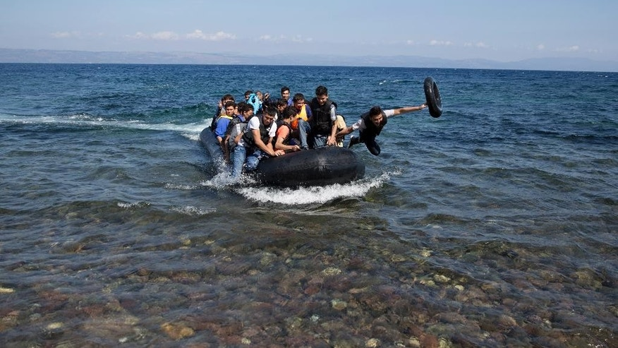 Afghan migrants arrive on the shores of the Greek island of Lesbos after crossing the Aegean sea from Turkey on a inflatable dinghy, Friday, Sept. 25, 2015. More than 260,000 asylum-seekers have arrived in Greece so far this year, most reaching the country's eastern islands on flimsy rafts or boats from the nearby Turkish coast.(AP Photo/Petros Giannakouris)