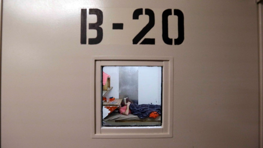 An inmate lies on a bunk reading in the psychiatric unit of the Pierce County Jail in Tacoma, Wash.