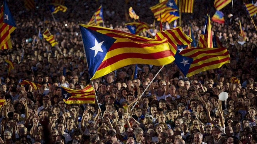 "Pro independence supporters wave ""estelada"" or pro independence flags during a rally of ""Junts pel Si"" or ""Together for YES"" in Barcelona, Spain, Friday, Sept. 25, 2015. Catalans vote Sunday in regional parliamentary elections that the breakaway camp hopes will give them a mandate to put their region on a path toward independence - a goal the Madrid central government says would be illegal.  (AP Photo/Emilio Morenatti)"