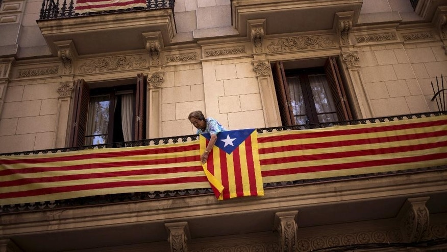 "In this Wednesday, Sept. 23, 2015 photo, a woman attaches an ""estelada"" or pro independence flag on her balcony in Barcelona, Spain.  Catalans vote Sunday in regional parliamentary elections that the breakaway camp hopes will give them a mandate to put their region on a path toward independence - a goal the Madrid central government says would be illegal.  (AP Photo/Emilio Morenatti)"