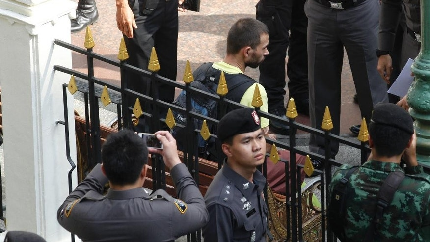 Police officers escort a key suspect in last month's Bangkok bombing, yellow shirt, identified as Adem Karadag sits on the chair where he left the bomb on it during a reenactment for the Aug. 17 bombing at Bangkok's popular Erawan Shrine  Saturday, Sept. 26, 2015. National Police Chief Somyot Poomphanmuang said Saturday that authorities are confident that the two men in custody, identified as Adem Karadag and Mieraili Yusufu, are the culprits who planted and detonated the bomb at the Erawan Shrine on Aug. 17, killing 20 people and injuring more than 120. (AP Photo/Sakchai Lalit)