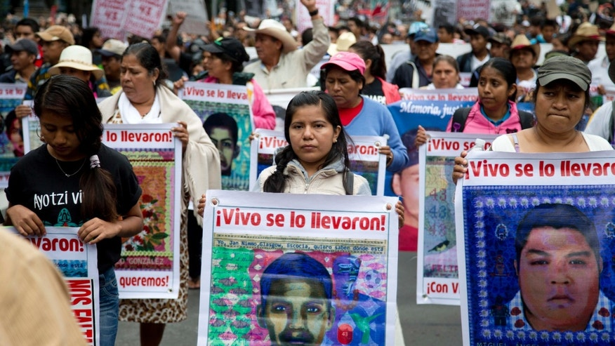 Relatives of the 43 missing college students hold images of their loved ones during a march  in Mexico City, on Sept. 26, 2015.