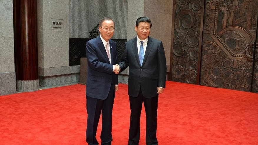 FILE - In this May 19, 2014 file photo, Chinese President Xi Jinping, right, shakes hands with United Nations Secretary General Ban Ki-moon, left, as they pose for photos on the eve of the fourth Conference on Interaction and Confidence Building Measures in Asia (CICA) summit at the Xijiao State Guesthouse in Shanghai, China. China's President Xi is poised to address the U.N. General Assembly for the first time on Monday, Sept. 28, 2015. (Mark Ralston/Pool Photo via AP, File)