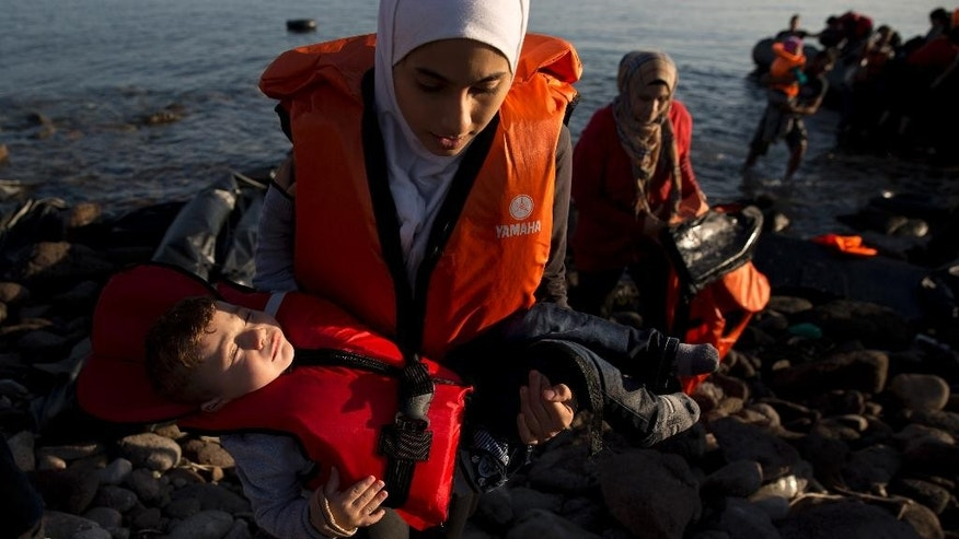 Syrian refugees arrive on the shores of the Greek island of Lesbos after crossing the Aegean sea from Turkey on a inflatable dinghy, Sunday Sept. 27, 2015. More than 260,000 asylum-seekers have arrived in Greece so far this year, most reaching the country's eastern islands on flimsy rafts or boats from the nearby Turkish coast.(AP Photo/Petros Giannakouris)