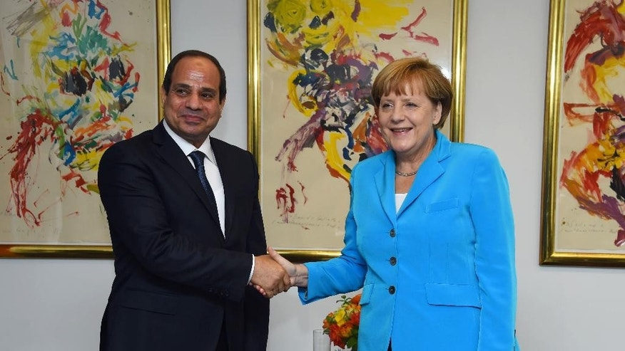 In this picture taken Friday, Sept. 25, 2015, provided by the office of the Egyptian Presidency, Egyptian President Abdel-Fattah el-Sissi, left, shakes hands with German Chancellor Angela Merkel during the meetings of the UN General Assembly in New York. The two discussed bilateral relations and the latest developments in Egypt, the Egyptian presidency said.  (Egyptian Presidency via AP) MANDATORY CREDIT