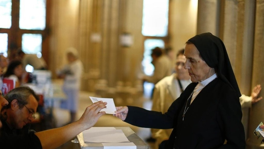 A nun prepares to vote at a polling station in Barcelona, Spain, Sunday Sept. 27, 2015. Voters in Catalonia go to the polls on Sunday to elect regional lawmakers, with pro-secession parties saying they will push for independence within 18 months if they win a majority in the 165-seat parliament, as most opinion polls predict they will. (AP Photo/Manu Fernandez)
