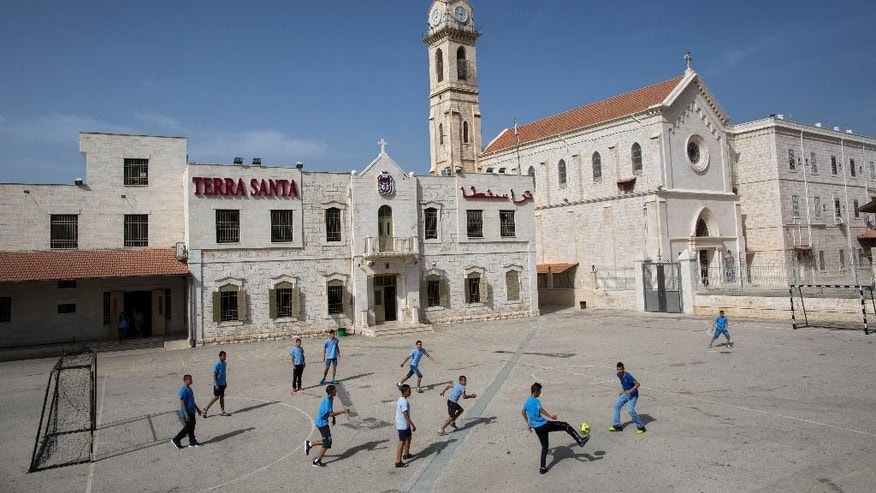 FILE - In this Tuesday, May 26, 2015 file photo, Arab Israeli Christian school children play soccer at the Terra Santa School in the mixed Jewish-Arab city of Ramle. Israel's Education Ministry says it has reached a settlement to end a nearly month-long strike by the nation's Christian schools. The Christian schools have been on strike since the school year began on Sept. 1 to protest cuts in government funding. Christian leaders have said the cuts amounted to discrimination. (AP Photo/Oded Balilty, File)